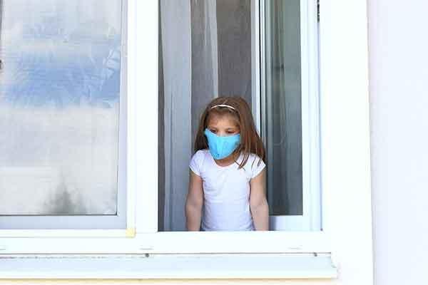 Girl Looking Through Window Wearing Mask